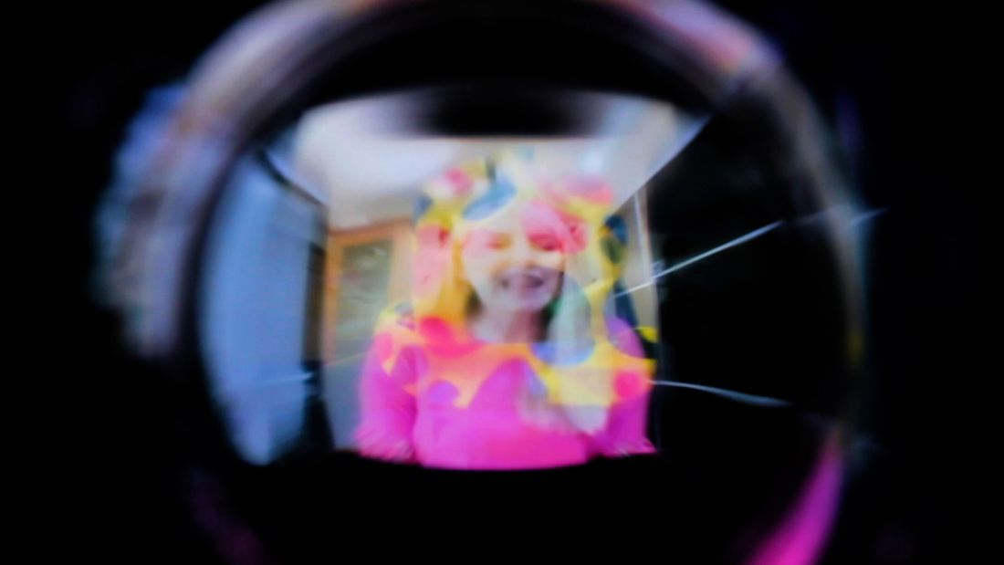 A blurred and light-distorted image down a dark camera lens of a smiling person with white skin wearing a bright pink top.