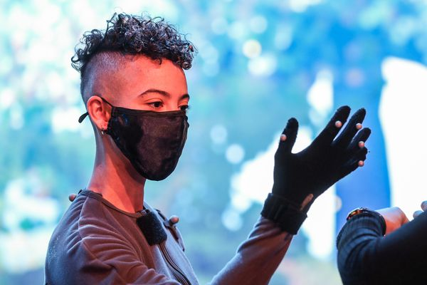 A person with curly black short hair with shaved sides wears a black mask and a grey motion capture suit and stands in front of a digital screen