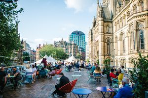 People sitting outside in the sunshine at tables in MIF's pop-up Festival Square in Manchester