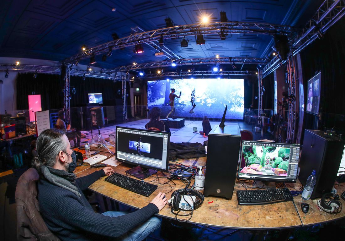 A mo-cap studio is seen from behind a bank of computer screens, an actor in a motion capture suit is seen on the stage, their posture mirrored by an avatar on a digital screen behind them
