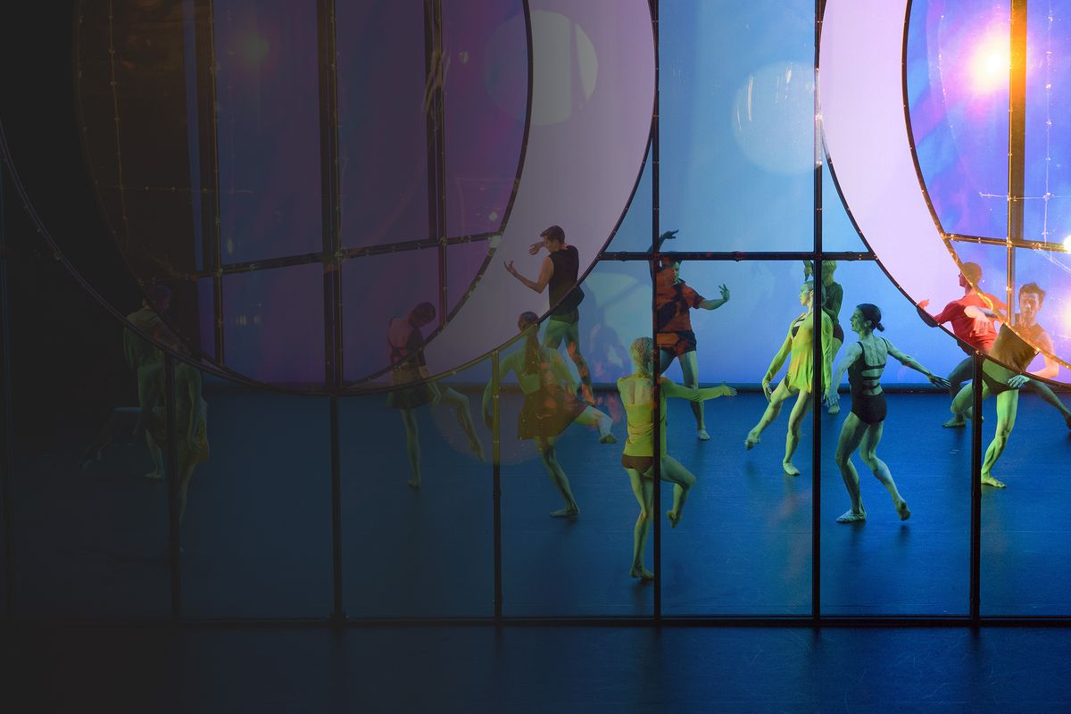 Group of dancers performing on a stage under coloured lights